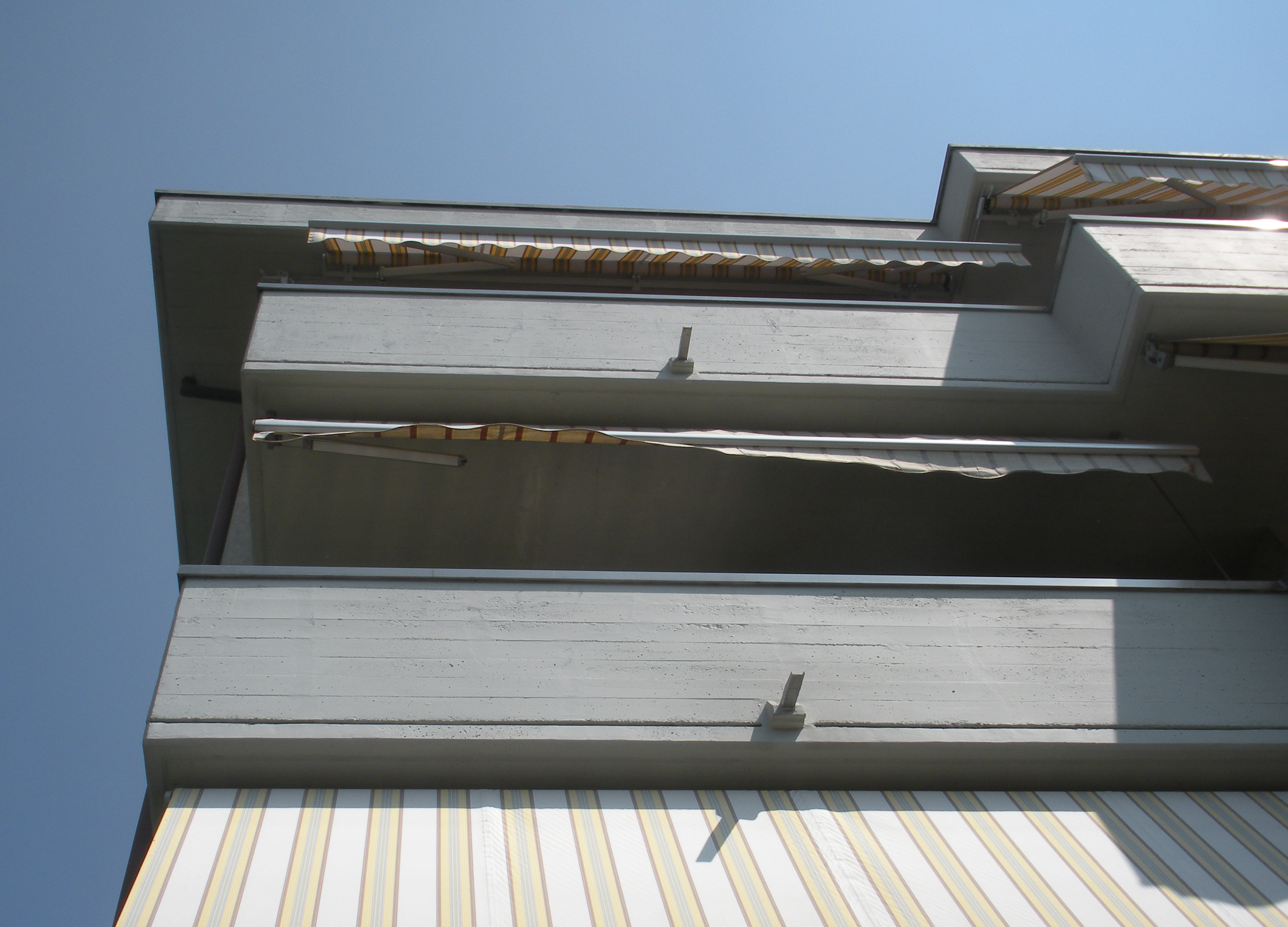 Particolare del restauro del cemento armato e della protezione pigmentata anti carbonatazione (Tinteggio protettivo) di un condominio - ITON SRL