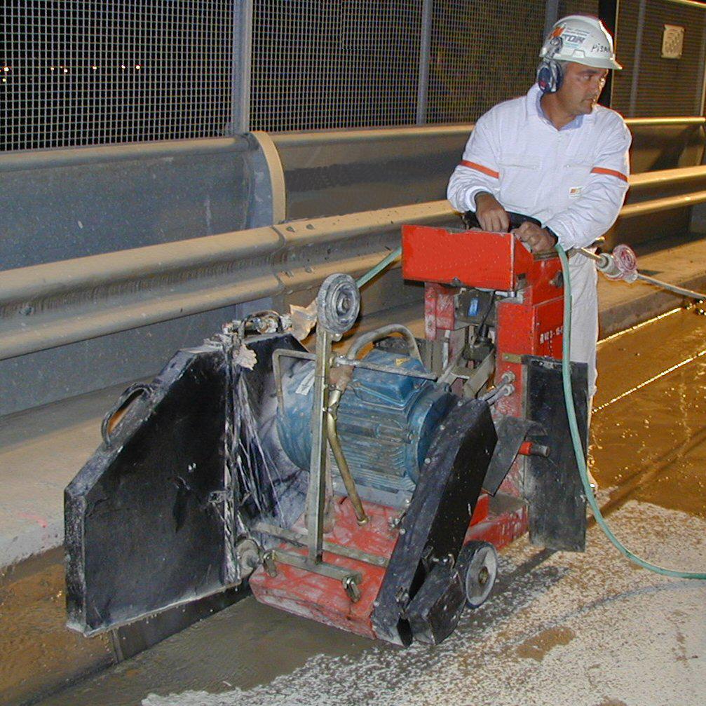 Tagliagiunti a disco diamantato. Taglio a pavimento di un impalcato in cemento armato, per il sezionamento in blocchi di un cavalcavia.